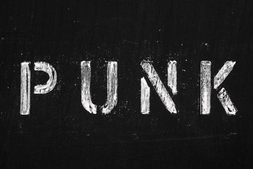 The word Punk in stencil letters on a used blackboard