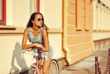 Beautiful young brunette woman sitting on a bike in old town