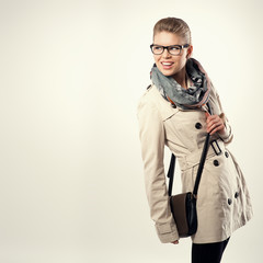 Pretty fashion girl in stylish coat and eyeglasses looking aside