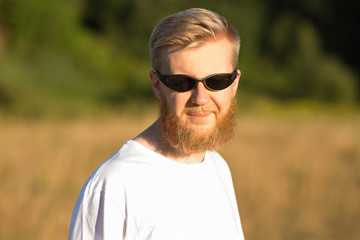 Young smiling bearded man in sunglasses