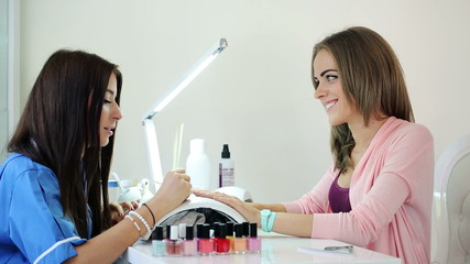 Woman chatting during finger nails painting with female client