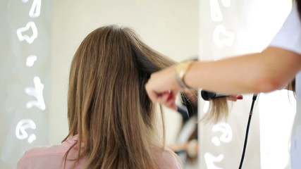 Hairdresser using straightener on beautiful woman hair