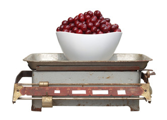 red cherry in a white cup on old mechanical scales isolated on w