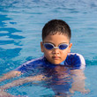 Cute little boy with his goggles on in swimming pool
