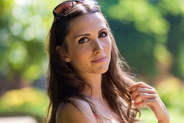 Beautiful woman with dark hair and brown eyes posing at garden.