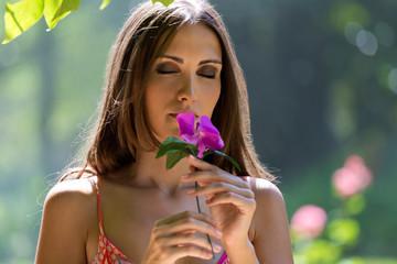 Young beautiful girl smells flowers, against green summer garden