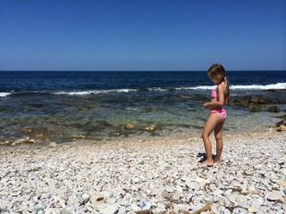 Spiaggia di pietre e bambina