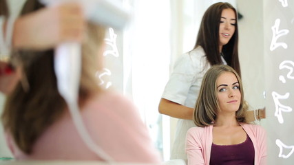 Hairdresser drying client hair with blow-dryer in hair salon