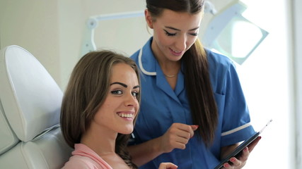 Happy client with worker with tablet computer in beauty salon