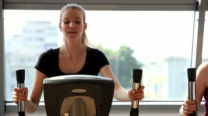 young blonde woman training in the gym, elliptical, smile