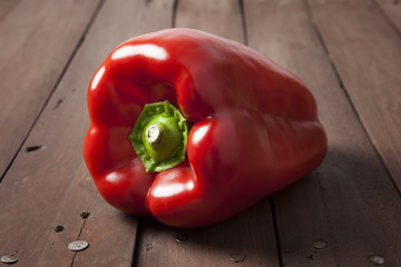 Red bell pepper on wooden brown table