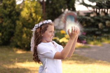 Uśmiechnięta dziewczynka ze świecącą  kulą w dłoniach.