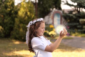 Radosna dziewczynka ze świecącą kulą w dłoniach.