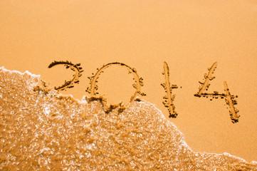 2014 inscription on the sand near sea