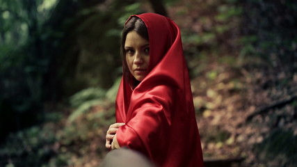 Serious beautiful mysterious woman, red riding hood in forest
