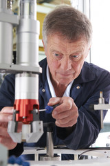 Engineer Working On Machine In Factory