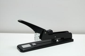 Single heavy stapler on white desk.