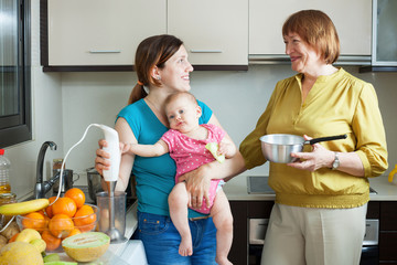 Happy women of three generations with blender