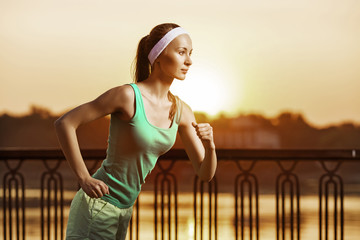 Running woman. Runner is jogging on sunrise. Female fitness