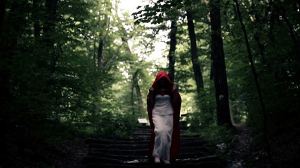 Dark, mysterious woman, red riding hood walking in the forest