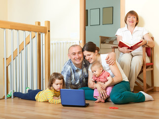 Happy family of three generations using blue laptop  in home int