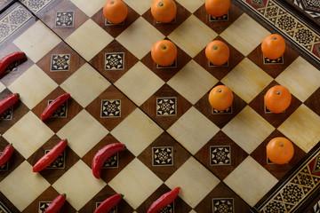 Tabuleiro de dama com pimenta e laranja