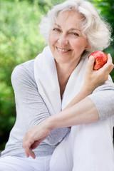 Sportliche Seniorin mit Apfel