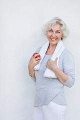 Aktive Seniorin nach dem Sport mit Apfel