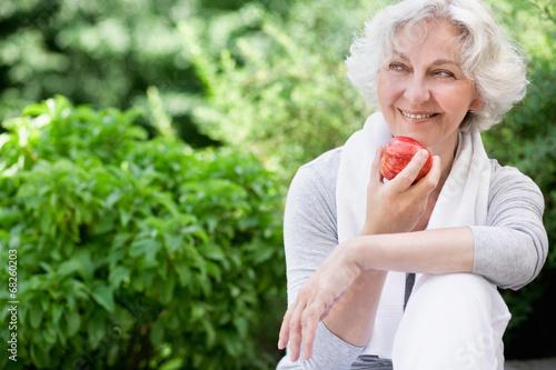 Leinwanddruck Bild Sportliche Seniorin mit Apfel
