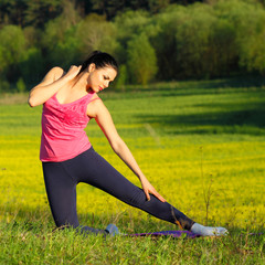 Yoga girl on the background of yellow field outdoors