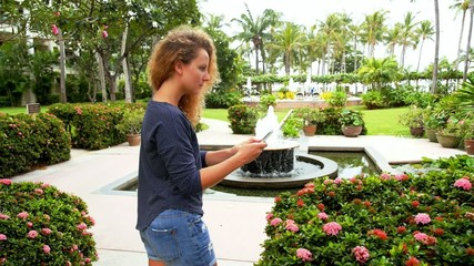 Young Woman Photographing Flowers Using Mobile Phone.
