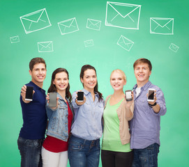 group of smiling students showing smartphones