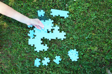 Hand holding puzzle piece on green grass background