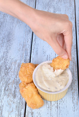 Hand dunks nuggets in sauce close-up