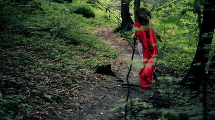 Chased red riding hood running away in the forest