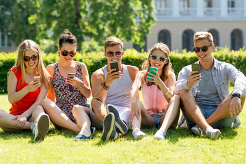 smiling friends with smartphones sitting on grass