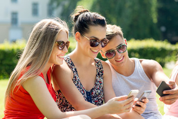 smiling friends with smartphones sitting in park