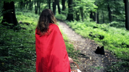 Red riding hood with basket walking in the forest