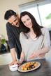 cheerful young couple preparing chocolate dessert in kitchen