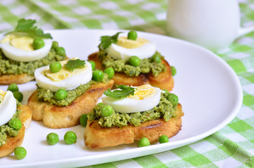 Toasts with basil pesto,eggs and green peas.