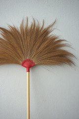 Brown broom on the concrete gray wall