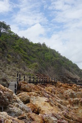 Wooden pathway with guardrail on cliff