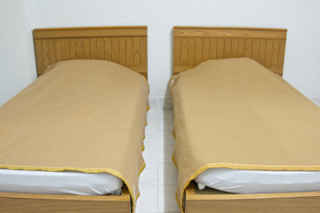 Twin brown bed and blanket on white mattress at hotel