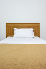 White pillow on brown bed and blanket at hotel