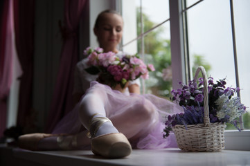 Ballet dancer sitting on windowsill holding flowers
