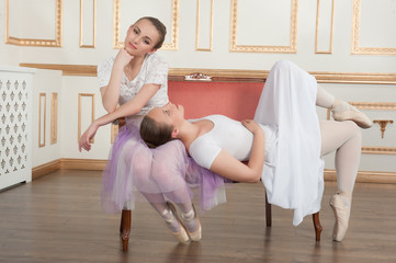 Two young beautiful ballet dancers sitting on sofa in classical
