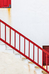 Red banister in front of a white wall