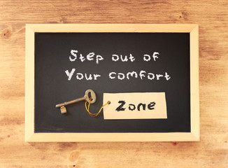the phrase step out of your comfort zone written on blackboard