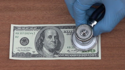 economist with stethoscope looking usa hundred dollar banknote