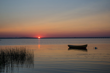 Lone rowboat in calm water at sunset